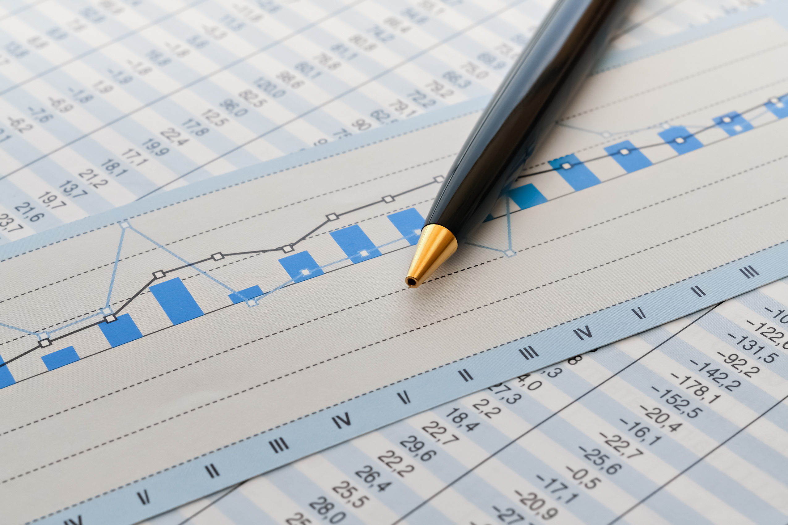 Closeup of a pen and business analysis spreadsheet with a graph